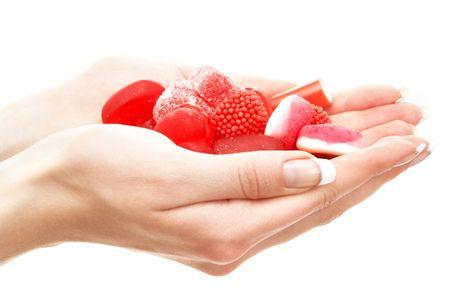 confect: Mani piene di rosso bonbons su bianco  Archivio Fotografico