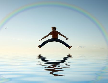 sporty man jumping under big colorful rainbow