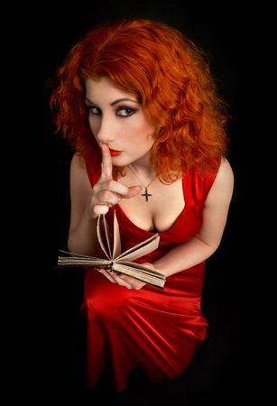 redhead religious lady with finger on lips photo