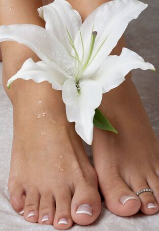 feet with madonna lily in spa (focus on flower) photo