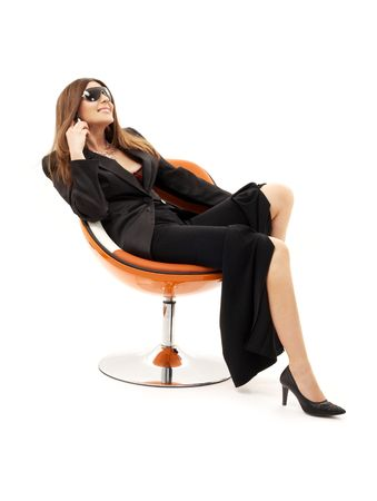 businesswoman with phone in orange chair over white Stock Photo - 1068231