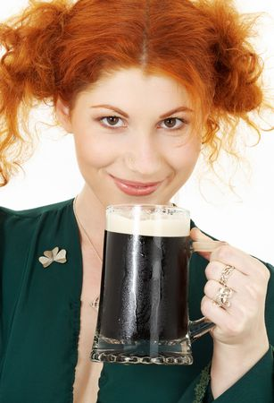 stout: redhead in green dress with a mug of irish stout beer Stock Photo