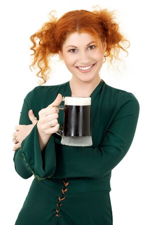 st patricks: redhead in green dress with a mug of irish stout beer Stock Photo
