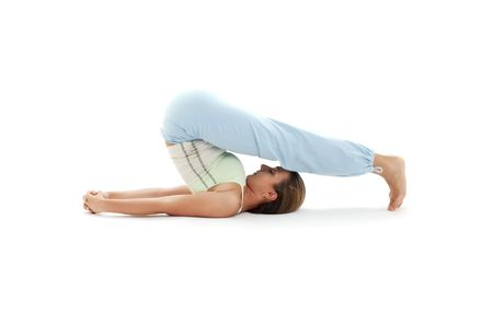 sporty girl practicing halasana plow pose over white photo