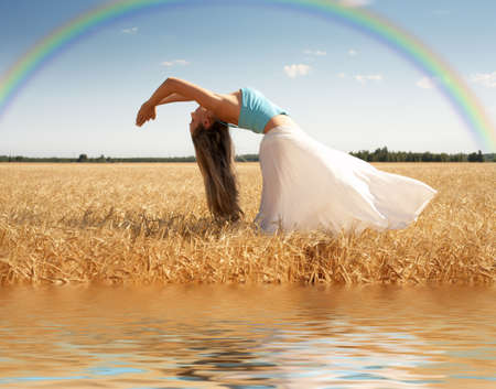 vivifying: stretching woman in the meadow with rainbow and water