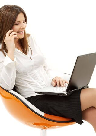 businesswoman with laptop and phone in orange chair over white photo