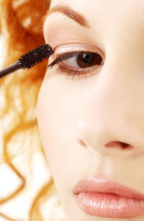 picture of lovely redhead applying black mascara  photo