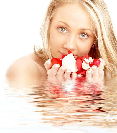 portrait of happy blond in spa with red and white rose petals photo
