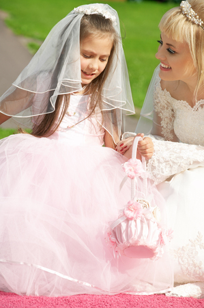 picture of happy bride and little bridesmaid photo