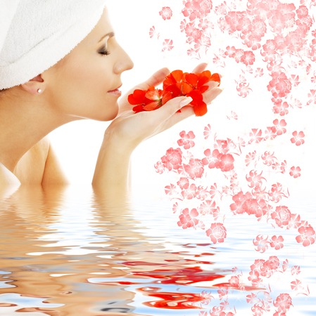 lovely woman smelling red flower petals in water Stock Photo - 1511989