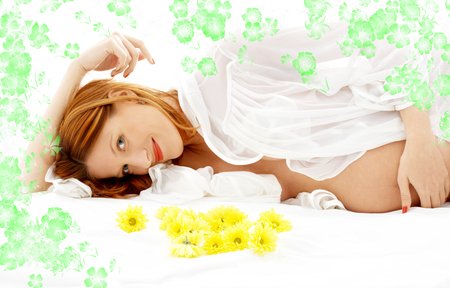 beautiful pregnant woman with flowers in bed photo