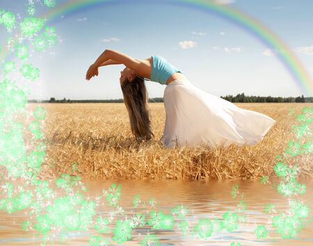 vivifying: stretching woman in the meadow with rainbow, water and flowers