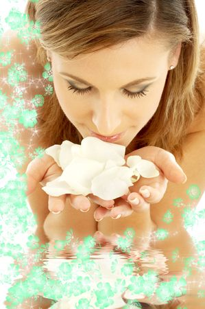 lovely woman in water smelling white rose petals
