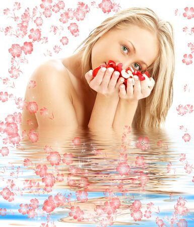 lovely blond with red and white rose petals in water with flowers photo