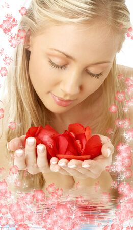 portrait of lovely blond in water with red rose petals photo