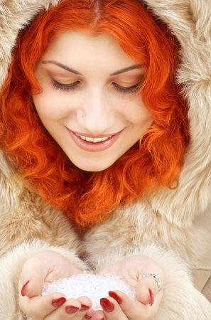 lovely redhead in fur with handful of ice photo