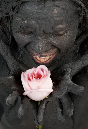 portrit of crying dirty girl holding pink rose photo