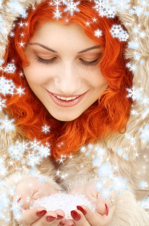 lovely redhead in fur with handful of ice and snowflakes photo