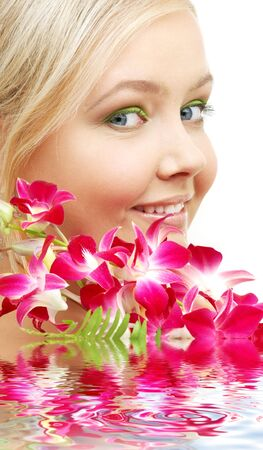 bright picture of lovely blond with orchid in water photo