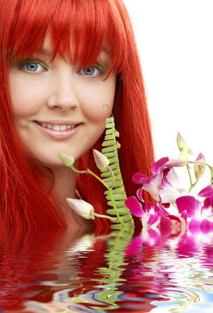 bright picture of lovely redhead with orchid in water photo