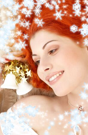 daydreaming redhead girl with white christmas bells and snowflakes photo