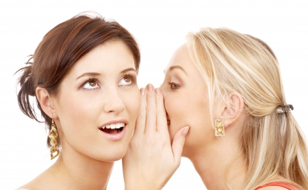 two happy young girlfriends talking over white Stock Photo
