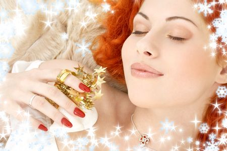 dreaming redhead girl with white christmas bells and snowflakes photo