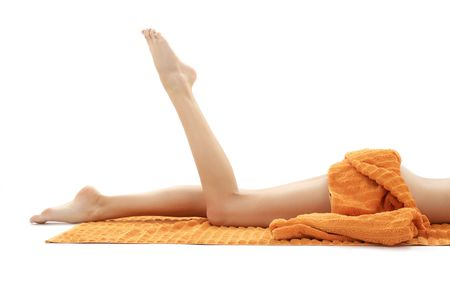 long legs of relaxed lady with orange towel over white Stock Photo - 2072624