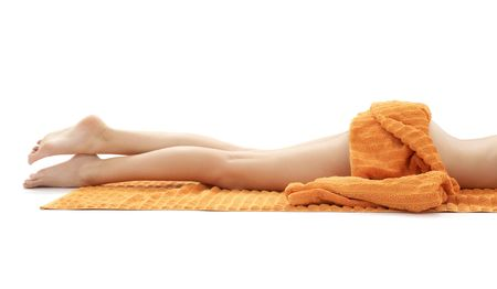 long legs of relaxed lady with orange towel over white Stock Photo