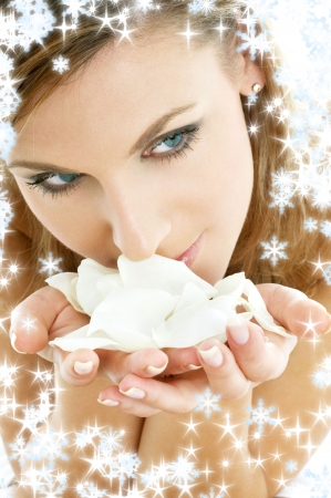 lovely woman in christmas spa smelling white rose petals photo