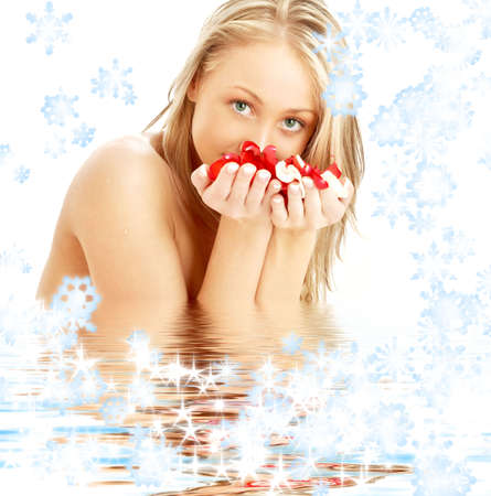 lovely blond with rose petals and snowflakes in water photo
