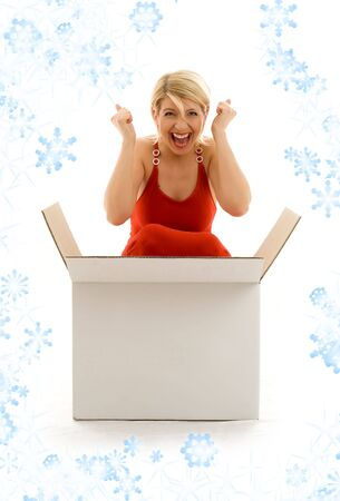 Happy girl in red dress with big blank white box and snowflakes photo