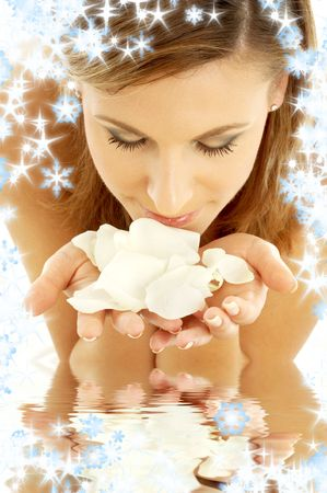 christmas scent: lovely woman in water smelling white rose petals and snowflakes