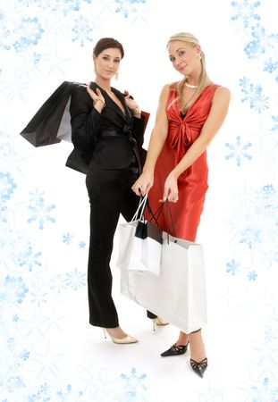 two happy girls with shopping bags and snowflakes photo