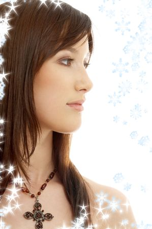portrait of lovely brunette with cross and snowflakes photo