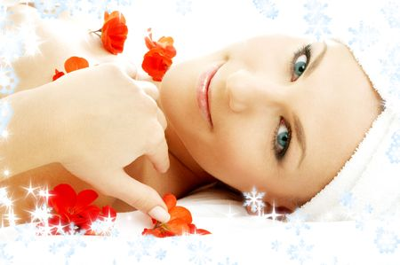 anti season: beautiful lady with red flower petals and snowflakes in spa
