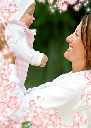 outdoor picture of happy mother with baby and flowers (focus on mom) photo