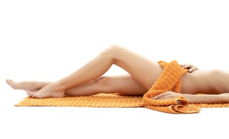 long legs of relaxed lady with orange towel over white Stock Photo - 2413092