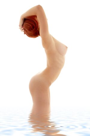 nude woman standing: classical nude picture of healthy redhead in water Stock Photo