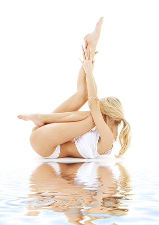 fit blond in white underwear practicing yoga on white sand photo