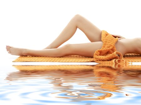 long legs of relaxed lady with orange towel on white sand Stock Photo