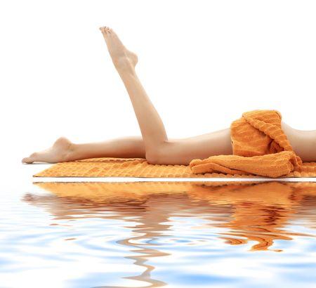 longues jambes de dame détendue avec la serviette orange sur le sable blanc