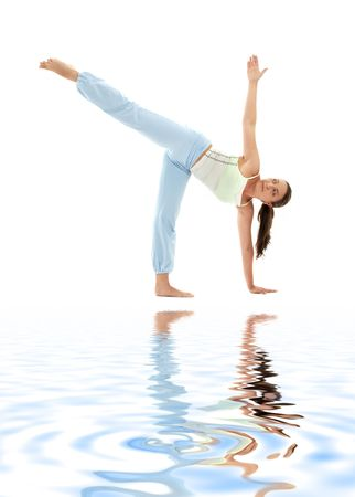 chandrasana: sporty girl practicing ardha chandrasana half moon pose on white sand Stock Photo
