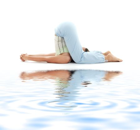sporty girl practicing halasana plow pose on white sand photo