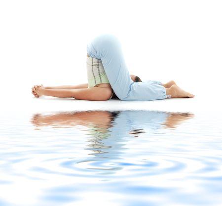 poise: sporty girl practicing halasana plow pose on white sand