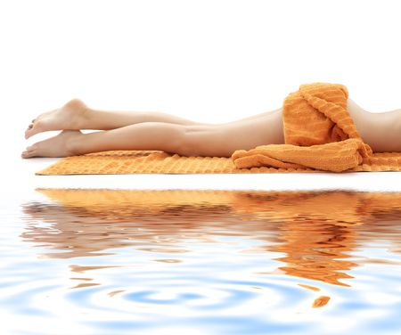 white towel: long legs of relaxed lady with orange towel on white sand Stock Photo
