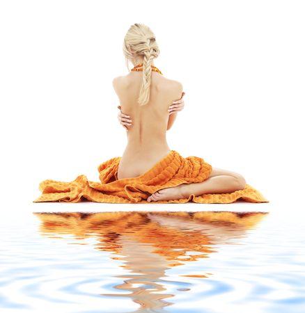 naaktstrand: mooie dame met oranje handdoeken over wit op wit zand