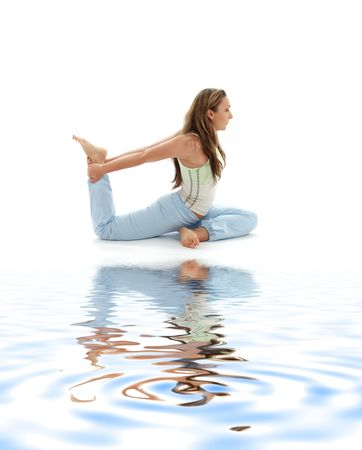 sporty girl practicing eka pada rajakapotasana one-legged king pigeon pose on white sand photo