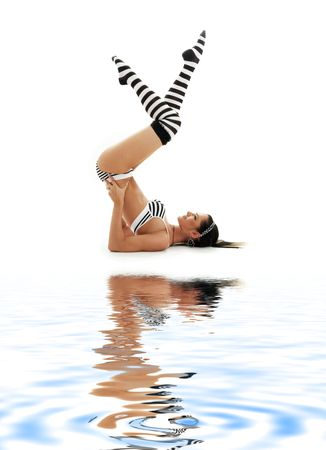 striped underwear girl practicing supported shoulderstand on white sand photo