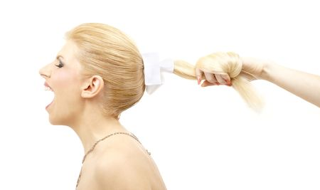 pulling hair: screaming blonde and female hand pulling her hair Stock Photo